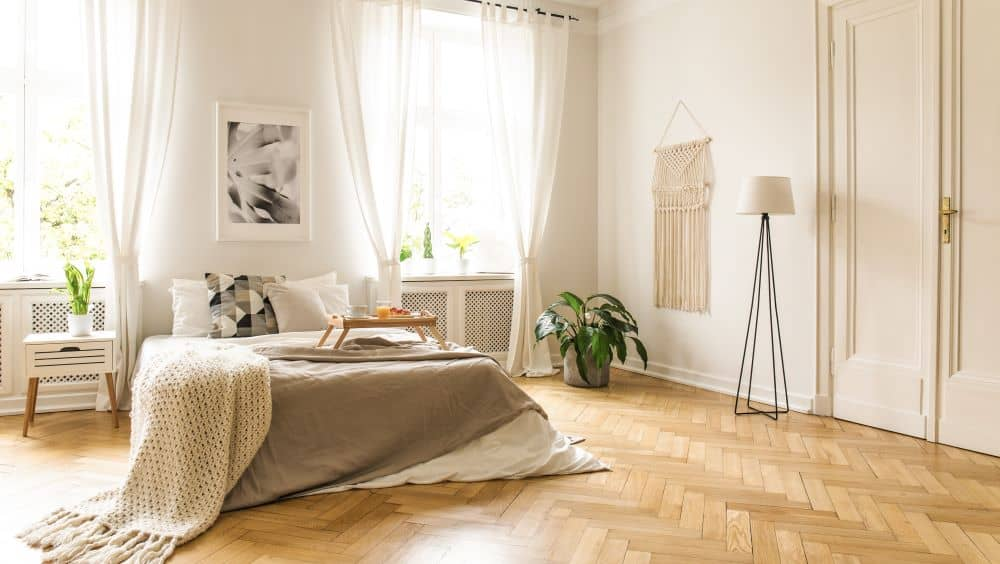 A cozy bedroom with wooden flooring in herringbone pattern.