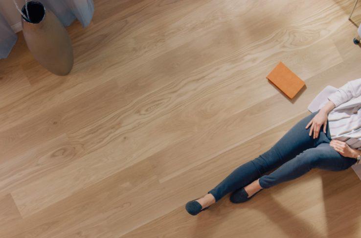 A women sitting on newly laid flooring.
